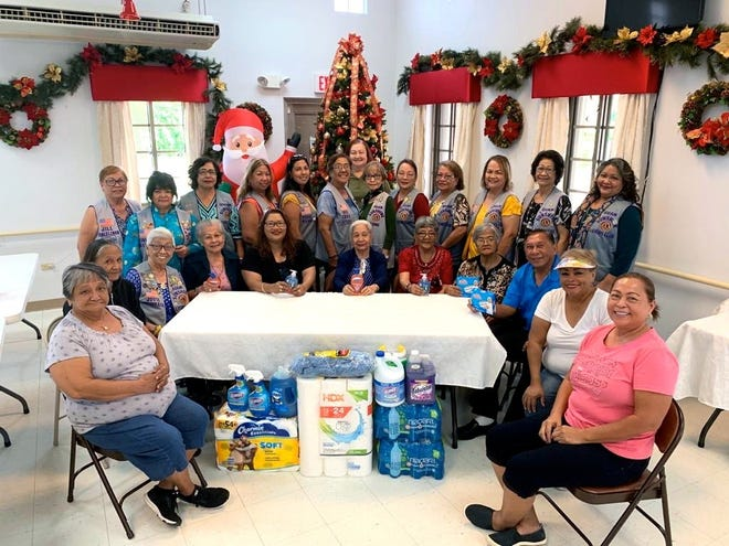 The Guam Sunshine Lions Club brought cheer, song, and supplies to the Santa Rita Community Center's senior citizens on Dec. 7. Recreational Leader, Cindy Baleto, seated fifth from left, is shown with the seniors and club members.