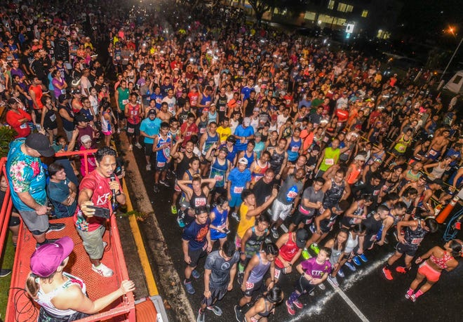 Race coordinator Manny Hechanova, bottom left, manages to capture a selfie, with race participants as his background, prior to the start of the 10-kilometer run of the 23rd annual Pay-Less Kick the Fat 5k/10k Run/Walk on Marine Corps Drive, near the Chamorro Village in Hagåtña on Saturday, Jan. 26, 2019.