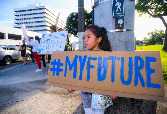 Six-year-old Zaia Vazcones stands with Micronesia Climate Change Alliance members and other supporters as they gather for a wave at the ITC Intersectionin Tamuning on Friday, Sept. 27, 2019. The wave was held in solidarity internationally, as part of the Global Climate Strike.