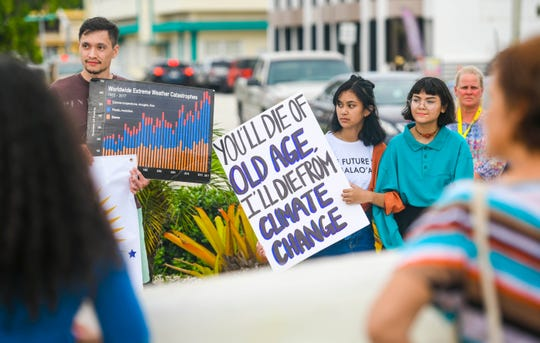 Supporters carry signs during a rally, hosted by the Micronesia Climate Change Alliance, to raise awareness of issues affect global climate change, in front of the Guam Congress Building in Hagåtña on Wednesday, Aug. 7, 2019. The group also protested against Guam Power Authority's plans to build a fossil fuel dependent power plant, instead of increasing options for renewable power sources.