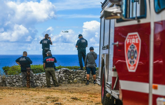 Guam Fire Department personnel watch as a Navy Helicopter Sea Combat Squadron 25 helicopter searches along the coastline near Talofofo Bay during a search for a missing spearfisherman on Wednesday, May 22, 2019. Fortunately the man was located and in good health with no emergency health care needed, said GFD spokesman Kevin Reilly.