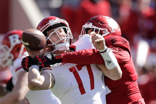 Rutgers quarterback Johnny Langan (17) fumbles as he is hit by Indiana defensive lineman Demarcus Elliott (94) during the first half of an NCAA college football game, Saturday, Oct. 12, 2019, in Bloomington, Ind.