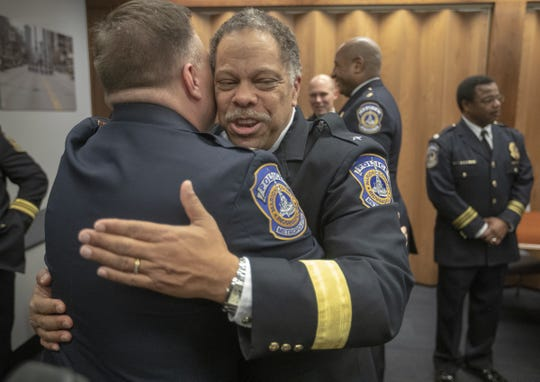 New Indianapolis Metropolitan Police Department chief Randal (Randy) Taylor (right) gets a hug from the new Assistant Chief Chris Bailey, after a swearing ceremony, Indianapolis, Tuesday, Dec. 31, 2019.