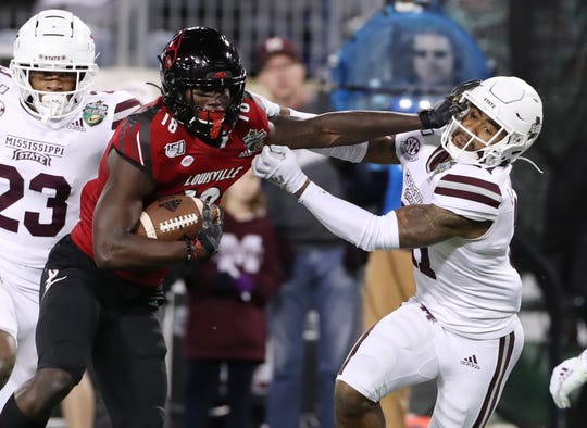 Justin Marshall (left) throws a stiff-arm against a Mississippi State defender in the 2019 Music City Bowl.