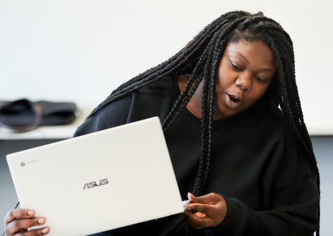Jefferson Community and Technical College student Shaqnika Taylor checks out her new Chromebook laptop from Louisville's Family Scholar House.