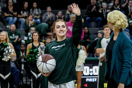 Michigan State guard Taryn McCutcheon waves to the crowd after she received a commemorative ball while being honored for surpassing 1,000 career points before the Spartans game against Nebraska on Tuesday, Dec. 31, 2019, at the Breslin Center in East Lansing.