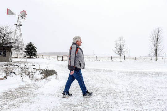 Gary Walters walks back from his barn on Tuesday, Dec. 31, 2019, at his home outside Charlotte. Walters is under contract to sell 126 acres of his property to Geronimo Energy. The company is proposing an 850-acre solar array in Benton Township.