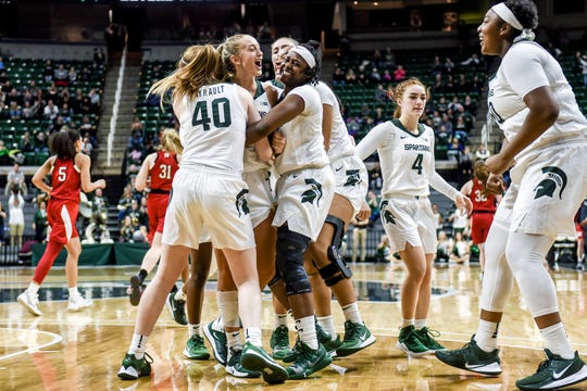 Michigan State's Tory Ozment, center, is surrounded by her teammates after tying up the game late during the fourth quarter on Tuesday, Dec. 31, 2019, at the Breslin Center in East Lansing.