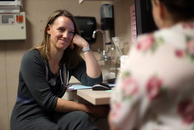 """Dr. Angela Gatzke-Plamann is seen at the Necedah Family Medical Center in Necedah, Wis., on Nov. 7, 2019, doing a check-in with Catina Stoflet, 35, who has been on medication-assisted treatment for seven months. """"There isn't another me just down the road. I'm the only one here,"""" says Gatzke-Plamann. """"So if I can fulfill that need, then I should do that. And I don't think that's something that urban or suburban physicians have to deal with."""""""