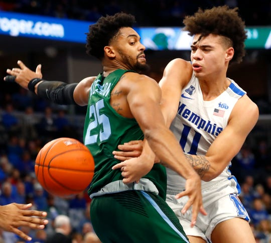 Memphis Tigers guard Lester Quinones squeezes a pass by Tulane Green Wave guard Christion Thompson during their game at the FedExForum on Monday, Dec. 30, 2019.