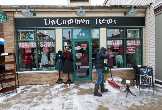 Snow is removed from the sidewalk Tuesday at Uncommon Items, 1316 E. Brady St. The store is set to close on Brady Street on Jan. 5 and move to a shared space in Walker's Point in the next few weeks.
