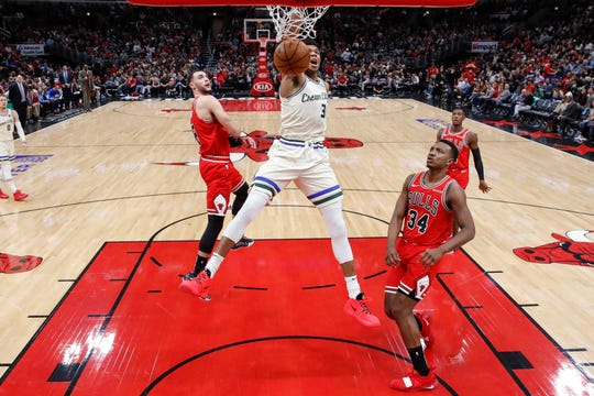 Bucks forward Giannis Antetokounmpo throws down a thunderous dunk as a trio of Bulls players looks on during the third quarter.