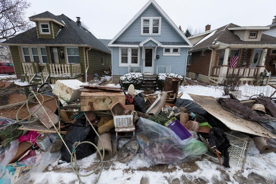 Water-damaged items from flooded basements wait to be picked up Dec. 31 in the 400 block of South 60th Street in Milwaukee. The flooding was caused by a water main break at Hawley Road just south of I-94.