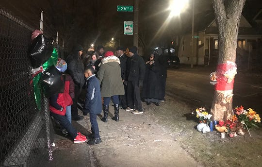 Mourners attend a vigil Monday night for the victims of the car crash Friday that killed four members of a family. Killed were Larry G. Williams Jr., 29; Ayana M. Hill, 22; Yana Williams, 2; and Larry G. Williams IV, 5 months.