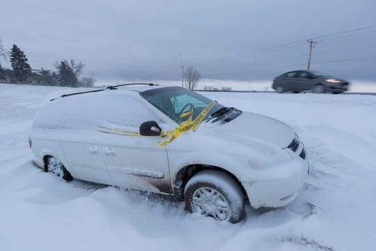 Motorists slowly pass a car that spun off into a ditch Tuesday on Highway 151 about eight miles north of Fond du Lac.