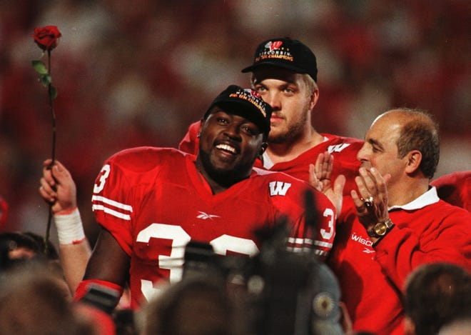 Ron Dayne, Chris McIntosh and coach Barry Alvarez celebrate on the field after Ron Dayne set the NCAA all-time rushing record Nov. 19, 1999.