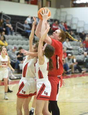 Norfork's Hannah Bryant catches a pass over two Lead Hill defenders on Monday at Harrison.