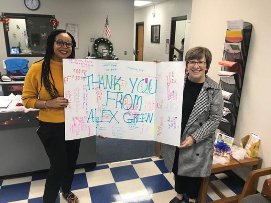 Two teachers from Alex Green Elementary had their wish lists fulfilled through the Adopt-a-Teacher initiative, including school counselor LaRhonda Cockrell, left. Also holding the sign is The Tennessean's Heather Cass.