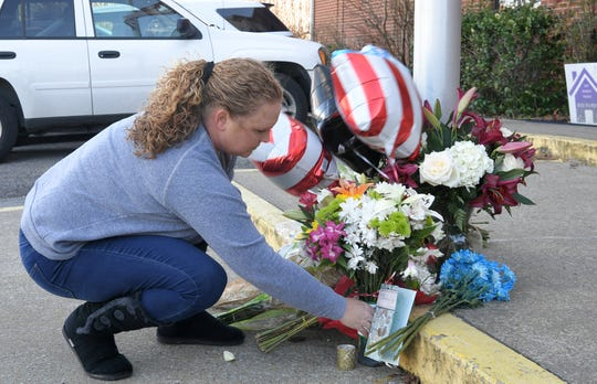 Melanie Calvert places flowers outside the Hendersonville Police Department on Tuesday, Dec. 31, 2019, to pay respects to Hendersonville police officer Spencer Bristol, who was killed in the line of duty on Monday, Dec. 30, 2019.