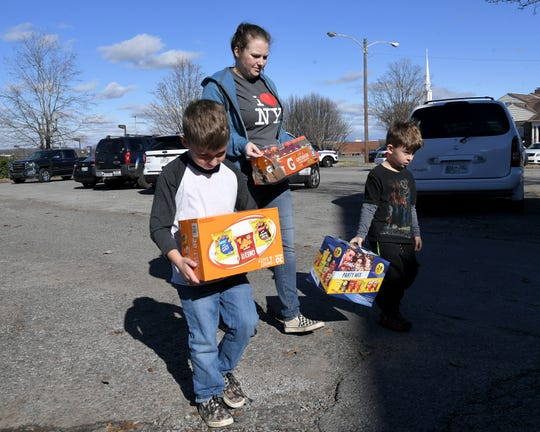 Paige Clark and two her sons, Charlie, 7, and Ender, 5, carry snacks and drinks to the Hendersonville Police Department on Tuesday, Dec. 31, 2019. Hendersonville Officer Spencer Bristol was killed in the line of duty the day before after being struck by a vehicle during a foot pursuit.