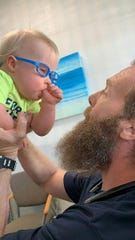Benedict Wardein, a toddler from Fort Myers, wears his new glasses to look at his father, Damien Wardein.