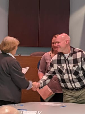 Scott Hite (right) shakes Buckeye Lake Mayor Peggy Wells' hand moments after being sworn in as the village's new fire chief on Sunday, Dec. 29, 2019.