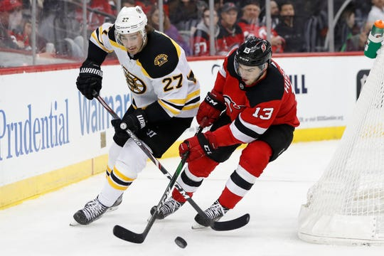New Jersey Devils center Nico Hischier (13) battles for the puck with Boston Bruins defenseman John Moore (27) during the second period of an NHL hockey game, Tuesday, Dec. 31, 2019, in Newark, N.J.