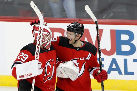New Jersey Devils center Travis Zajac (19) celebrates with Devils goaltender Mackenzie Blackwood (29) after the Devils defeated the Boston Bruins in a shootout in an NHL hockey game, Tuesday, Dec. 31, 2019, in Newark, N.J.