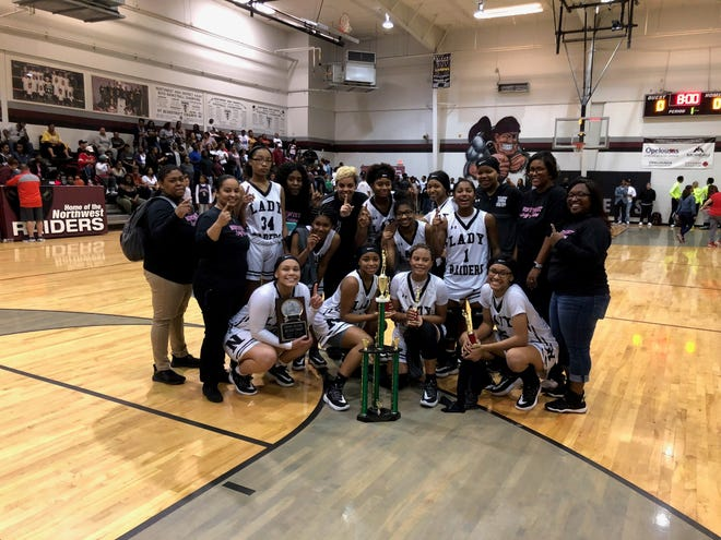 The Northwest High girls' team celebrates a hosted-tournament victory Sunday night over Lafayette Christian. Raiders' senior forward Khahli Malone scored 17 points including eight during the final two minutes that helped seal the team's second tournament title in two weeks.