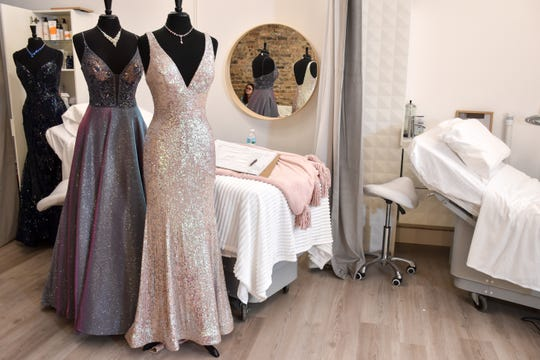 Dresses stand in front of beds used by customers of Jo Rich Beauty on Tuesday, Dec. 31, 2019. The beauty bar celebrated its grand opening after growing from a mall kiosk.