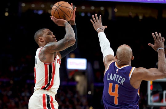 Portland Trail Blazers guard Damian Lillard, left, shoots over Phoenix Suns guard Jevon Carter during the first half of an NBA basketball game in Portland, Ore., Monday, Dec. 30, 2019. (AP Photo/Craig Mitchelldyer)