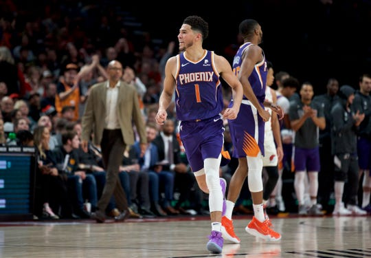 Phoenix Suns guard Devin Booker reacts after scoring against the Portland Trail Blazers during the second half of an NBA basketball game in Portland, Ore., Monday, Dec. 30, 2019. The Suns won 122-116. (AP Photo/Craig Mitchelldyer)
