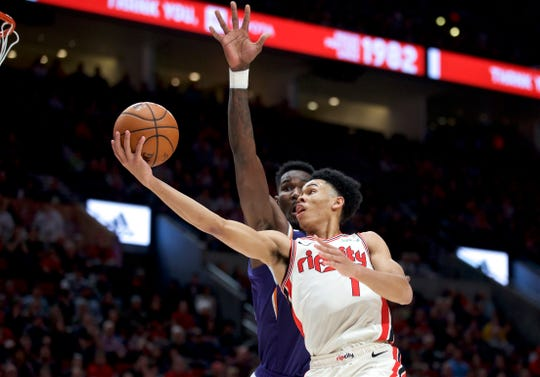 Portland Trail Blazers guard Anfernee Simons, right, shoots over Phoenix Suns center Deandre Ayton during the second half of an NBA basketball game in Portland, Ore., Monday, Dec. 30, 2019. (AP Photo/Craig Mitchelldyer)