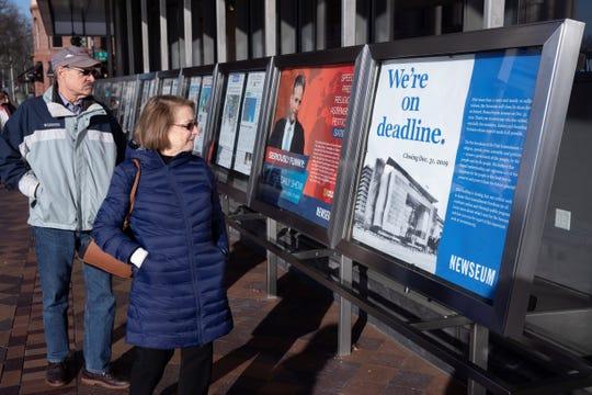 Personas miran las portadas de hoy fuera del Newseum en Washington, DC, el 26 de diciembre de 2019. Debido a luchas financieras insostenibles, el Newseum, que ha estado abierto en su ubicación actual durante más de once años y ha visto casi diez millones de visitantes, cerrará permanentemente puertas en la ubicación de Pennsylvania Avenue, el 31 de diciembre de 2019.
