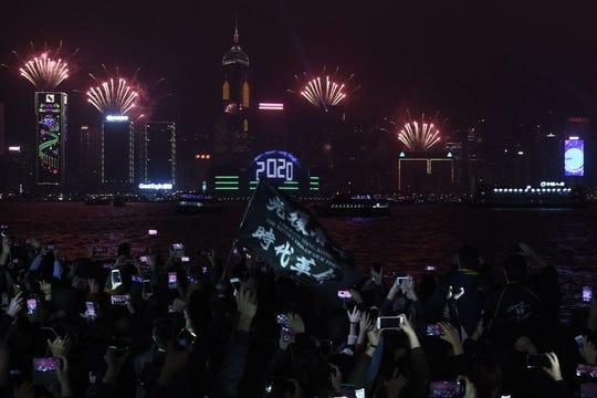 Los manifestantes a favor de la democracia en una manifestación y los juerguistas usan sus teléfonos en el paseo marítimo del distrito de Tsim Sha Tsui mientras los fuegos artificiales explotan sobre Hong Kong el 1 de enero de 2020.