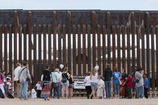 Familiares y amigos del joven mexicoamericano Carlos Lamadrid, quien falleció a manos de un agente de la Patrulla Fronteriza, estiran una pancarta el jueves 21 de marzo 2013, en el muro fronterizo que divide a Estados Unidos y México cerca de la ciudad fronteriza de Douglas en Arizona.