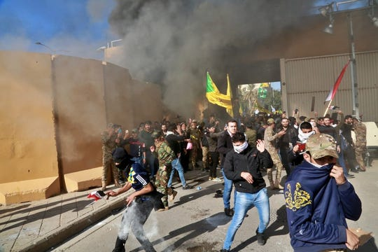 U.S. soldiers fire tear gas towards protesters who broke into the U.S. embassy compound, in Baghdad, Iraq, Tuesday, Dec. 31, 2019. Dozens of angry Iraqi Shiite militia supporters broke into the U.S. Embassy compound in Baghdad on Tuesday after smashing a main door and setting fire to a reception area, prompting tear gas and sounds of gunfire. (AP Photo/Khalid Mohammed)