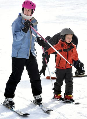 Marie Brown of Baltimore and her son Luke, 6, make their way to a lift at Roundtop Mountain Resort Tuesday, Dec. 31, 2019. Marie was teaching her son to ski. The resort has 14 trails open and eight lifts operational in spite of warm winter weather.ÊBill Kalina photo
