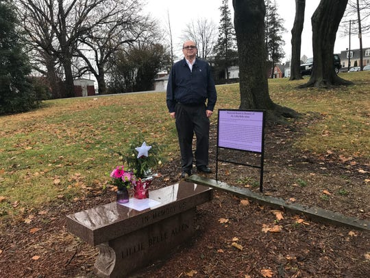 The bench in front of Bob Mann memorializes Lillie Belle Allen, killed in 1969 during the York riots. Facing her bench is one for Henry Schaad, also killed then. The purple sign beside Mann explains who Allen was and why she was killed; another describes Schaad. He created the markers because so many people have stopped him at the park to ask who these two people were. He doesn't want people to forget them. Mayor Michael Helfrich said the city intends to create permanent markers for this site.