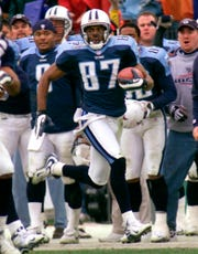 Tennessee Titans wide receiver Kevin Dyson (87) returns a kickoff for a touchdown in the fourth quarter of an AFC wild card game against the Buffalo Bills, in Nashville, Tenn. Looking on from the sideline is Titans quarterback Steve McNair (9), left foreground. Dyson sped 75 yards down the left sideline with a lateral from Frank Wycheck on a kickoff for the winning touchdown with 3 seconds remaining, lifting the Tennessee Titans to a 22-16 playoff victory over the stunned Buffalo Bills.