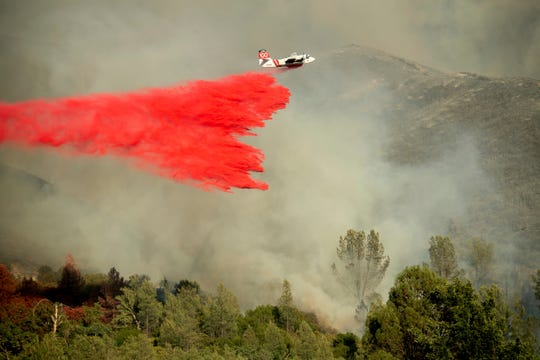 In this June 24, 2018, file photo, an air tanker drops retardant on a wildfire burning above the Spring Lakes community near Clearlake Oaks. California regulators on Tuesday. Dec. 31, 2019, said they have streamlined the state's permit process to make it faster to approve tree-thinning projects designed to slow massive wildfires that have devastated communities in recent years.
