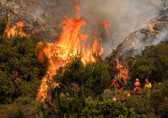 In this Sept. 2, 2017, file photo, a crew with California Department of Forestry and Fire Protection battles a brush fire on the hillside in Burbank. California regulators on Tuesday. Dec. 31, 2019, said that they have streamlined the state's permit process to make it faster to approve tree-thinning projects designed to slow massive wildfires that have devastated communities in recent years.