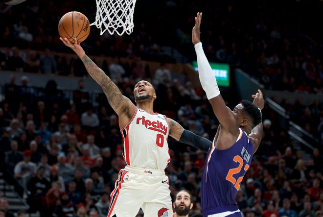 Portland Trail Blazers guard Damian Lillard, left, shoots over Phoenix Suns center Deandre Ayton during the second half of an NBA basketball game in Portland, Ore., Monday, Dec. 30, 2019. The Suns won 122-116.