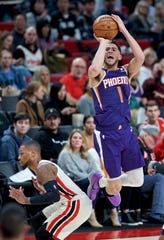 Phoenix Suns guard Devin Booker, right, shoots over Portland Trail Blazers guard Damian Lillard during the second half of an NBA basketball game in Portland, Ore., Monday, Dec. 30, 2019.