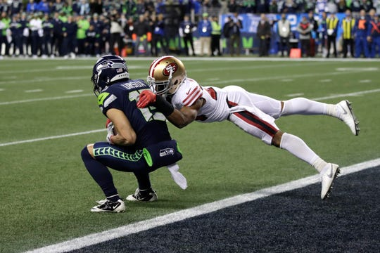 Seattle Seahawks' John Ursua, left, makes a catch at the one-yard line to give the team a first down with less than a minute left as San Francisco 49ers' K'Waun Williams tackles during the second half of an NFL football game, Sunday, Dec. 29, 2019, in Seattle. The 49ers won 26-21.