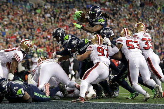 Seattle Seahawks running back Marshawn Lynch, top, leaps to score a touchdown against the San Francisco 49ers during the second half of an NFL football game, Sunday, Dec. 29, 2019, in Seattle. The 49ers won 26-21.
