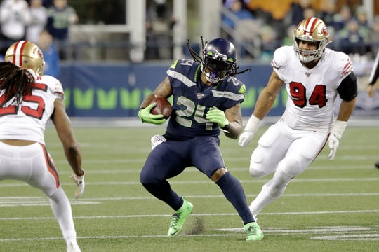 Seattle Seahawks' Marshawn Lynch (24) carries between San Francisco 49ers' Richard Sherman (25) and Solomon Thomas (94) during the second half of an NFL football game, Sunday, Dec. 29, 2019, in Seattle.