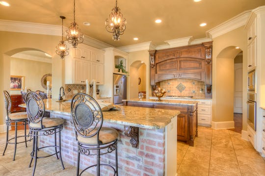 A granite breakfast bar provides extra seating for meals in the kitchen.