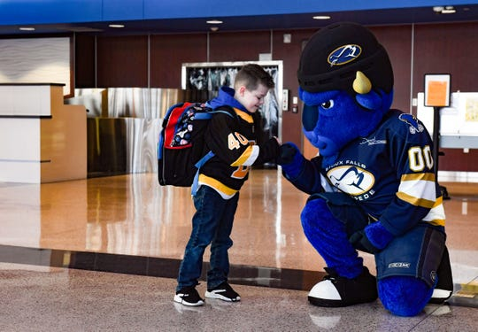 Ryker Hovey, 7, fist-bumps Stomp, the Sioux Falls Stampede mascot, on Tuesday, Dec. 31, at the Sioux Falls Regional Airport.