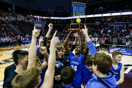 Greenwood's Aminu Mohammed hoists the Gold Division trophy after the Bluejays won the Gold Division championship in the Blue and Gold Tournament on Monday, Dec. 30, 2019.